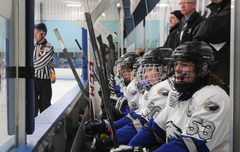 """Senior Captain Alex Schnieder watches from the bench as the hockey team takes on Grosse Pointe South High School. """"Bonding this preseason really has helped with our team chemistry,"""" Schneider said. """"We became friends, rather than just teammates."""" As of press time, the team began the season with a 3-1 record, their only loss coming  Grosse Pointe South High School."""