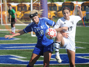Junior Paige Duda fights for the ball against a Grand Blanc player in a regional championship game.