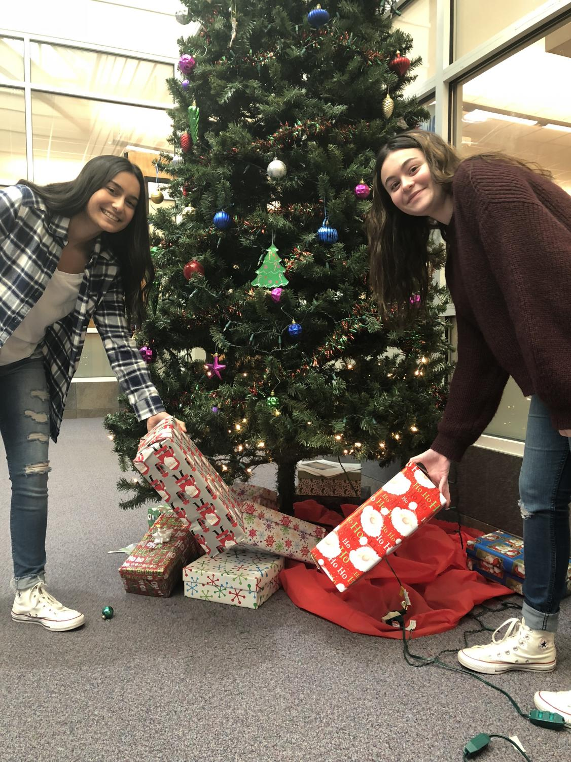 Junior Alyssa Battani and junior Sophia Asta place their wrapped gifts under the Christmas tree.