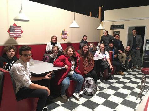 Film teacher Josephine Braun and the students on the trip sit on a movie set.