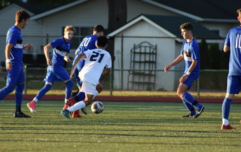 The boys varsity soccer team tries to surround the ball.
