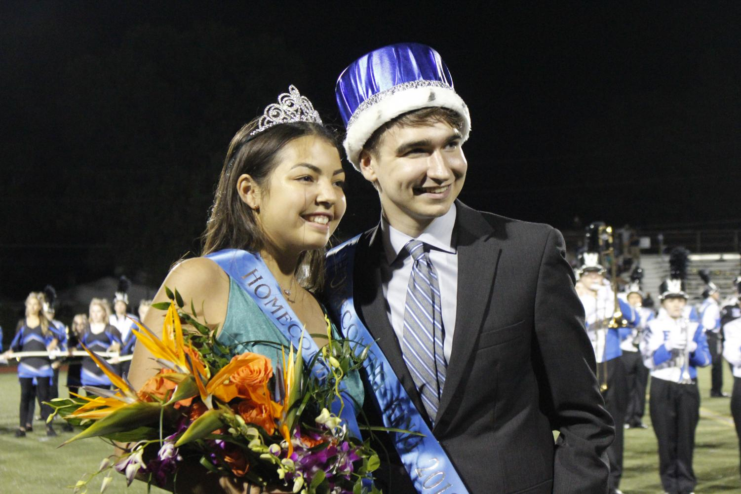 Homecoming king and queen Iain Robb and Carina Hanna pose for photos at the homecoming football game.