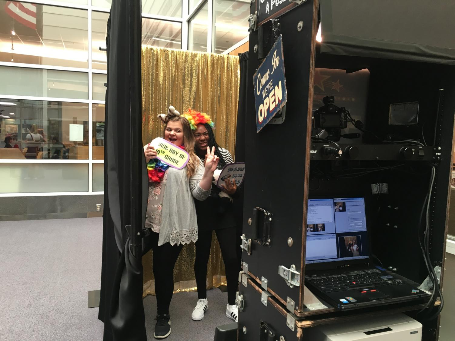 Sophomores Bella Arini and Ayoka Razaki take a picture in the photo booth to remember their first day of 10th grade.