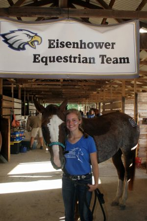 Finishing up the horse show, sophomore Kendall Westgate stands with her horse Paisley under a sign.