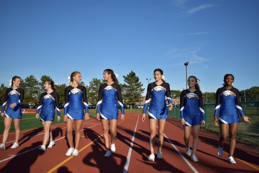 """A group of cheerleaders walk down the track towards their coach. """"I felt happy to cheer in the game,"""" sophomore base Haley Walters said. Walters injured her knee during a practice and worried she would not be allowed to cheer, however, she was given permission to and she cheered the game with no issues."""