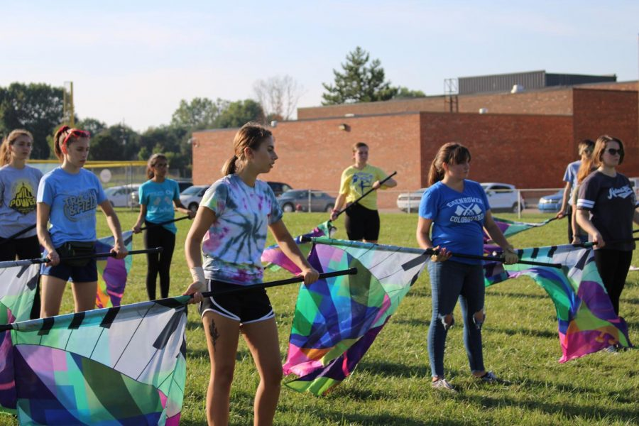 """As color guard prepares for their game at practice, senior color guard member Nicola Carlisi struggles spinning with a sprained wrist. She sprained it while spinning her rifle and couldn't participate during practice or the shows for two weeks  """"It really sucked because I like spinning pregame,"""" Carlisi said."""