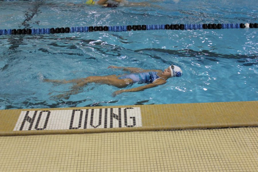 In+anticipation+of+upcoming+swim+meets%2C+counties%2C+divisions%2C+and+the+state+finals%2C+junior+Varsity+swimmer+Julianna+Scharret+prepares+and+focuses.+This+season+she%E2%80%99s+focused+on+being+the+fastest.+%E2%80%9CI+usually+sing+songs+just+in+order+to+take+my+mind+off+it.%E2%80%9D%0A