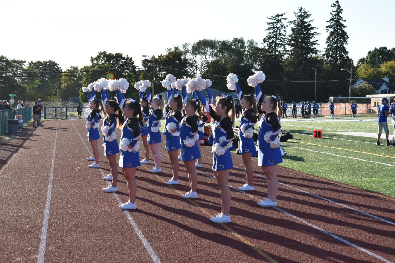 "Calling a chant to the crowd, freshman cheerleaders fire up the football players and crowd at Swinehart Field. ""In competitive season I'm looking forward to new challenges and new bonds with different people,"" freshman Olivia Sugameli said. The freshmen are considered JV athletes for the competitive season."