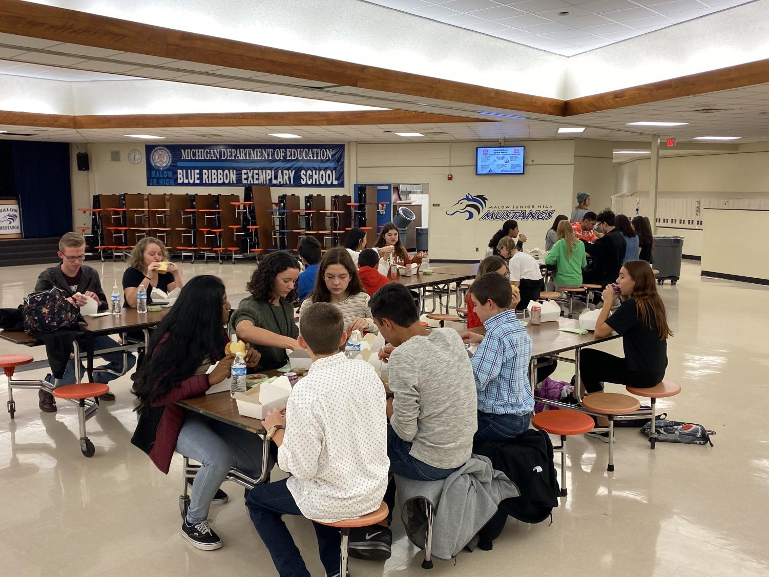 """While the French students enjoy a catered dinner at Malow Jr. High, they also take the time to talk with their peers. Some of the older students thought it was exciting to see the next group of kids. """"[My favorite part was] seeing some of the other french students from here and the next generation of French students,"""" sophomore Mina Metzler said."""
