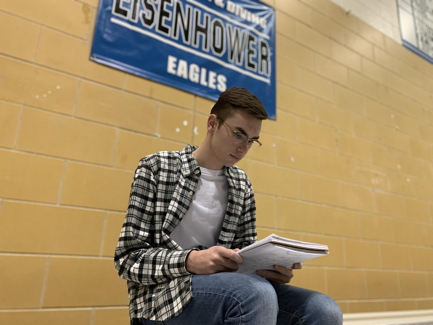 """While studying with free time before practice, senior swimmer Michael Hagen makes sure he knows the material for his Wednesday exam. Michael practiced dryland exercises after studying with the meets being the week of exams. """"I'm excited to see how we do and how we can improve times,"""" Hagen said."""