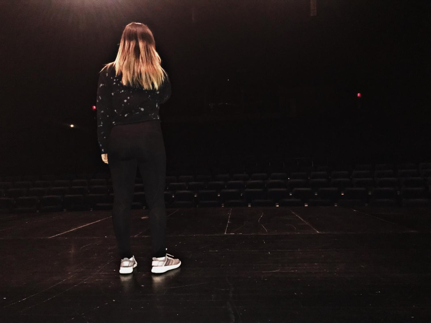"""Standing center stage, junior soloist Emily Chriss rehearses her song for the vocal pops concert. """"I can get nervous when I'm performing, but I push through the nerves and keep going,"""" Chriss said. She auditioned with the song """"Always remember us this way"""" this year after being chosen last year to sing in the concert."""