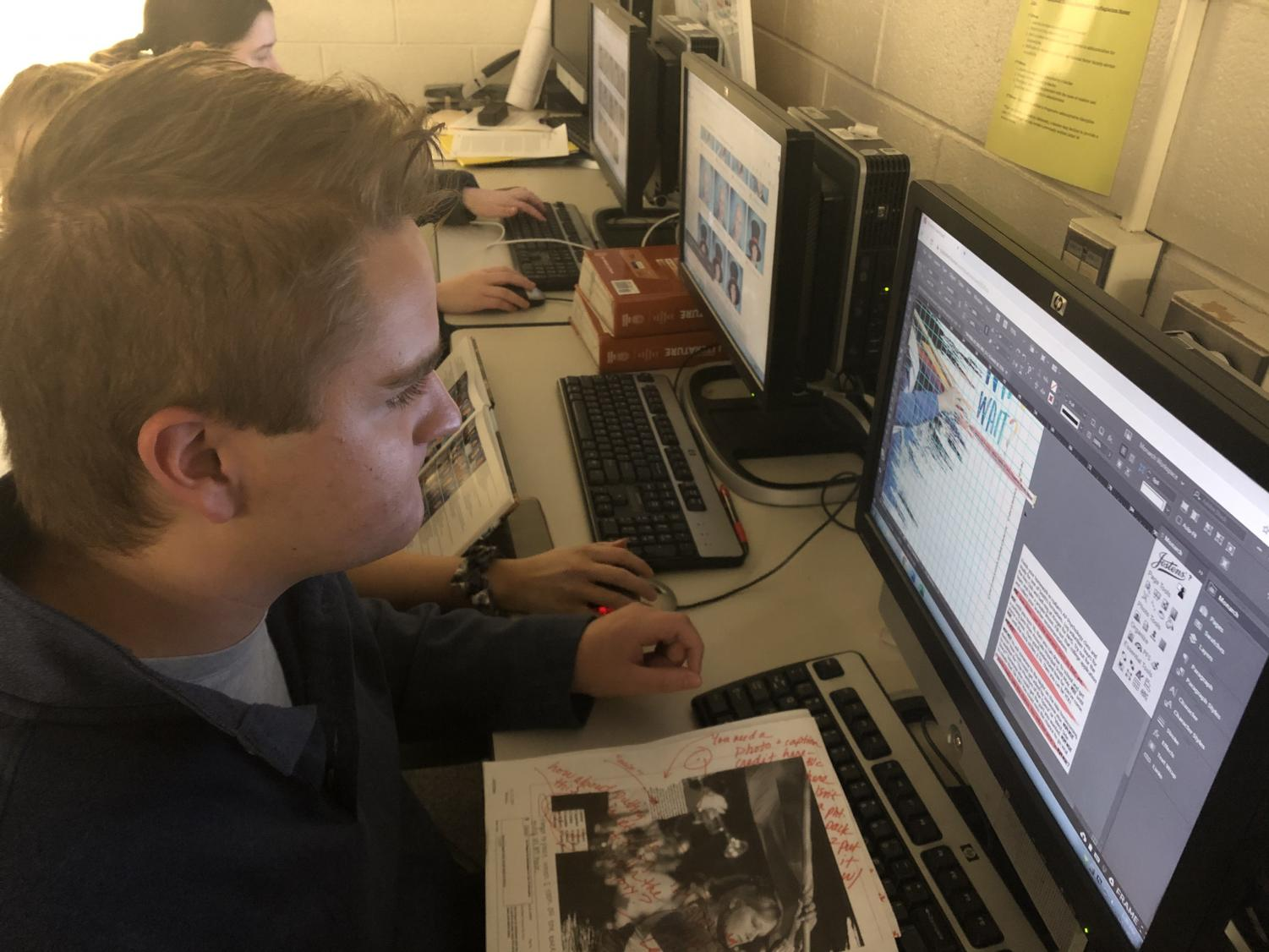 """Engulfed in his work on a spread, senior yearbook Editor-in-Chief Anthony Berkimer continues to engage with his yearbook spread and begins publishing it. """"It meant a lot to me because we put in a lot of work and it was nice to see that it paid off,"""" Berkimer said. The yearbook spread ended up winning second and third place for advertising in Quill and Scroll."""