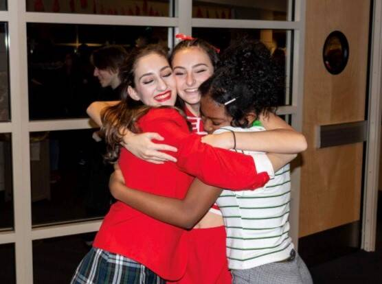 "As she finishes up the last show of ""High School Musical: On Stage,"" junior Olivia Steele shares a hug with her two friends, junior Sydney Townsend and junior Carly Irwin. ""I have family relations with a lot of them [Ike students], so I was able to connect deeper with a lot of them individually,"" Steele said. Steele realized even though she loved her private school, her public school changed her life for the better."