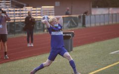 Throwing the ball back onto the field, senior Brandon Hineman plays in the varsity soccer game.