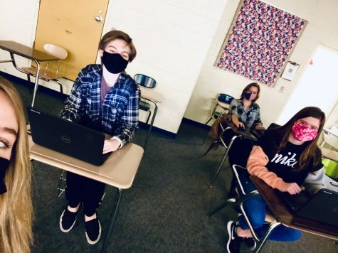 """Junior Danielle Carlisi sits with her friend Lauren Devereux. """"My favorite part about face to face school is getting to see people I haven't gotten to see in a while,"""" Carlisi said."""