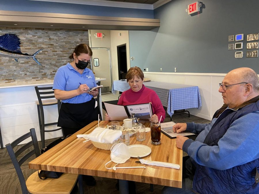 "Ocean Breeze server Lucy Sinistaj serves a table of guests for the first time in over two months. ""I was so excited [when I found out restaurants would reopen],"" Sinistaj said. ""I love everybody; I love all the customers that come in. I"