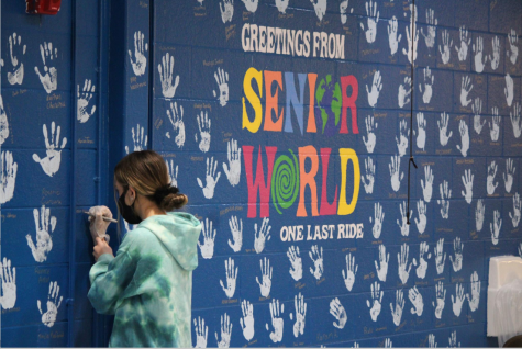"""After being separated and distant during the months of remote learning, seniors place their hand on the wall to partake in the senior wall tradition. """"I love the tradition and this year it means so much more, as it could be the closest these kids are to each other. It is absolutely so great to give this normal to the seniors,"""" student council advisor Amber Bronson said. The wall was completed on Feb. 5th."""